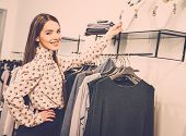 Young smiling woman in clothes showroom