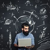 Bearded Man With Laptop Thinks About Space