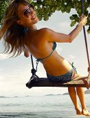 Yong lady having fun on the swing on tropical beach