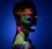 Woman sensual posing in fluorescent paint makeup