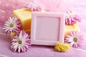 Bars of natural soap and fresh flowers on color wooden background