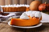 picture of pumpkin pie  - Composition of homemade pumpkin pie on plate and fresh pumpkins on wooden background - JPG