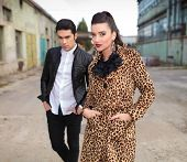 Fashion couple posing with their hands in pockets near old factory.