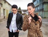 Fashion woman wearing a animal print coat, pulling her collar while looking at the boyfriend over the shoulder.