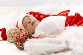 Little baby boy sleeping in santa hat with christmas decoration around him.