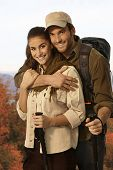 Happy young couple outing in autumn countryside, embracing, holding trekking poles.