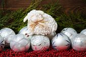 White christmas balls and  nice sheep with wooden background