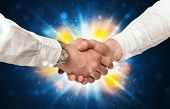 Two business men shaking hands with a successes agreement with explosion
