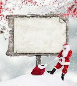 Empty wooden board with copy-space for text with Santa Claus and sack of gifts