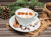 cup of cappuccino near Christmas tree with cones