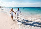 Happy couple running on the beach. Caribbean vacation