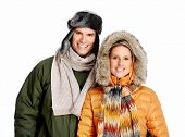 Happy couple in winter clothing isolated over white background.