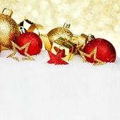 Red and golden christmas balls and decoration on snow