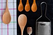 wooden spoons, metal grater and tablecloth over blackboard background