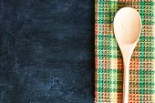 wooden spoon and tablecloth over blackboard background