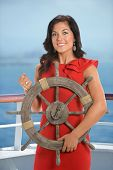 Businesswoman holding ship wheel with ocean in background