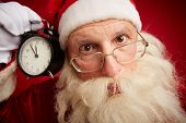 Puzzled Santa holding clock showing five minutes to xmas and looking at camera