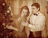 Couple on party near Christmas tree.