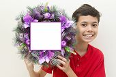 Young boy excited while holding purple Christmas wreath.