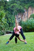 sporty woman stretching her lower back muscle by bending forward and twisting to one side