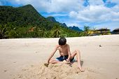 Young boy having fun outdoors playing in the sand by the beach in tropical island
