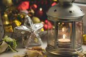 Christmas still life: lantern with burning candle and New Year tree decorations. Shallow depth of field. Aperture 2.8