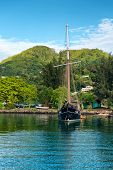 MAHE, SEYCHELLES - 21 OCTOBER 2014 - Vintage Fishing Vessel Sailing at the Island Beach of Seychelles with Fresh Looking Huge Mountains at the Background on 21 October 2014.