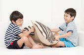 pic of pillow-fight  - Little sibling boy playing pillow fighting on sofa - JPG