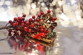 Decorative Christmas background with berries, cinnamon and bokeh lights