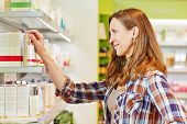 Elderly attractive woman buying cosmetics in a drugstore