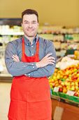 Smiling salesman standing with his arms crossed in a supermarket