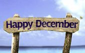 Happy December sign with a beach on background
