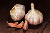 Garlic and cloves on old wooden background