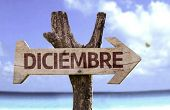 December (In Spanish) sign with a beach on background