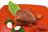bbq : beef (pork) steak garnished with green lettuce and red chili hot pepper on red plate isolated over white background