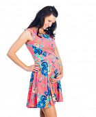 Young pregnant woman in pink dress isolated on white background