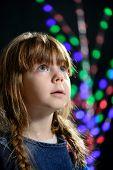 the little girl against a dark background looks aside