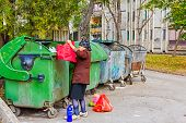 foto of dumpster  - Homeless woman is searching for food in garbage dumpster - JPG