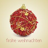 an ornamented red christmas ball and the sentence frohe weihnachten, merry christmas in german, on a beige background, with a retro effect