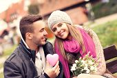 A picture of a couple on Valentine's Day in the park with flowers and heart