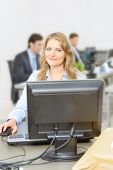 Woman working at her desk, with people working at the background