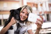 Young woman making a selfie with her dog