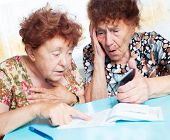 Two old women consider receipts. Surprised Female counts bill