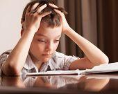 Boy doing homework. Sad child