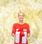 christmas, holidays, valentine's day, celebration and people concept - smiling woman in red clothes with gift box over yellow lights background