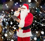 christmas, holidays, technology and people concept - man in costume of santa claus with tablet pc computer over snowy night city background