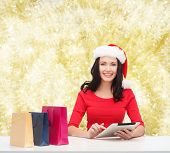 christmas, technology and people concept - smiling woman in santa helper hat with shopping bags and tablet pc computer over yelolow lights background