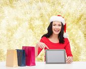 christmas, holidays, technology, advertising and people concept - smiling woman in santa helper hat with shopping bags and tablet pc computer over yellow lights background