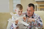 father and son assembling airplane toy at modern home living room indoor