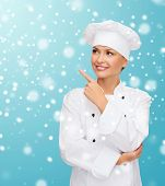 christmas, cooking, holidays and people concept - smiling female chef, cook or baker pointing finger up over blue snowy background